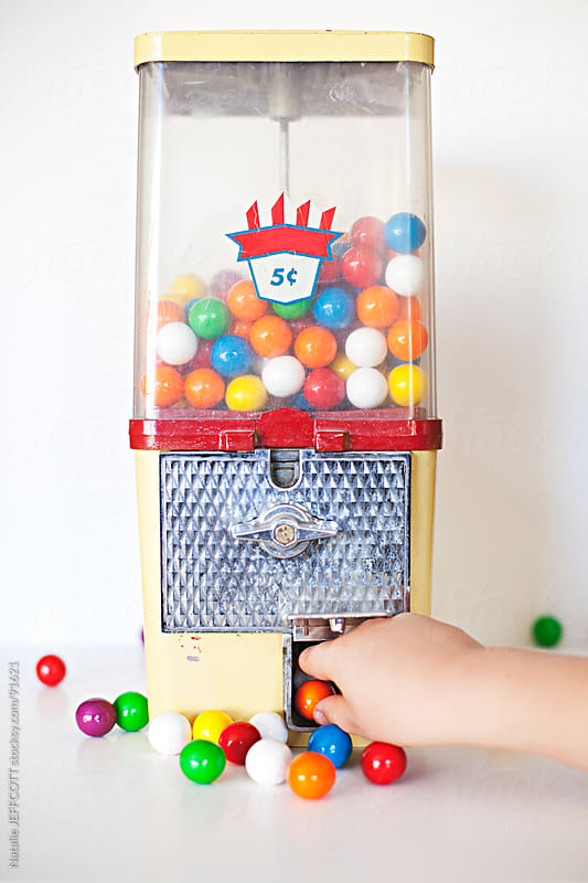 hand reaching into gum ball machine by Natalie JEFFCOTT for Stocksy United