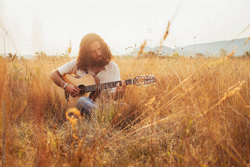 Bearded Young Man With Long Hair Playing Guitar in Dry Grassland by Julien L. Balmer for Stocksy United