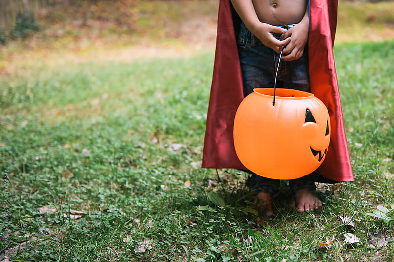 toddler in cape costume waits with halloween pumpkin in hand by Tara Romasanta for Stocksy United