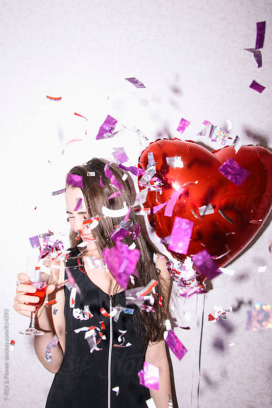 Young woman holding heart balloon and glass of champagne by Danil Nevsky for Stocksy United