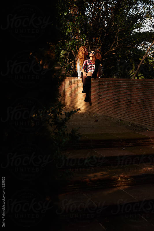 Two young women relaxing together on fence in park by Guille Faingold for Stocksy United