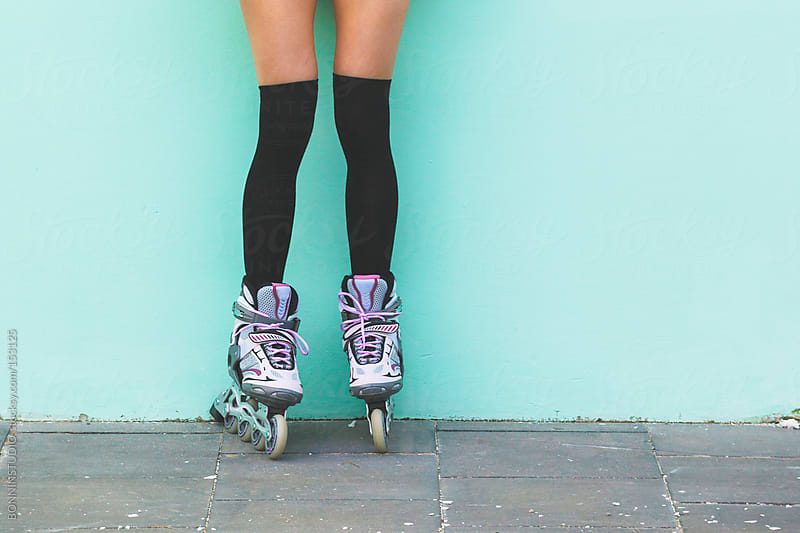 Close up of a roller girl standing in front a turquoise wall. by BONNINSTUDIO for Stocksy United