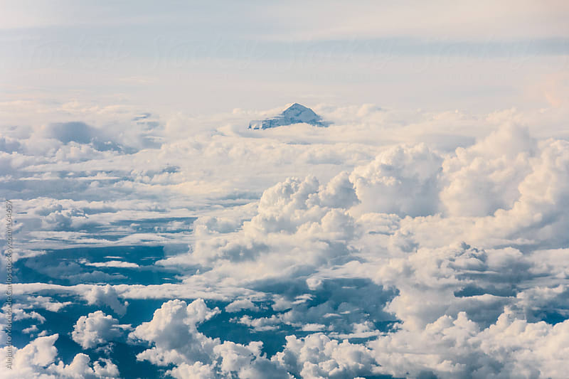 Clouds and mountain peak over clouds, aerial view of sky by Alejandro Moreno de Carlos for Stocksy United