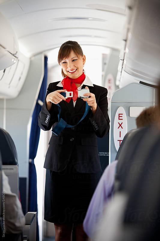 Airplane: Stewardess Demonstrates Seat Belt by Sean Locke for Stocksy United