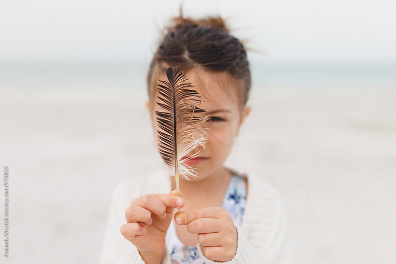 Little girl examining a feather found on the beach, feather in focus by Amanda Worrall for Stocksy United