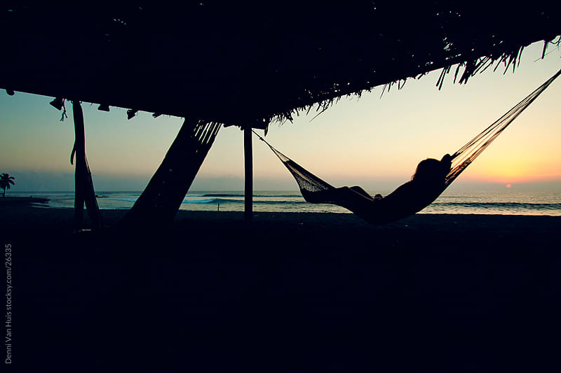 Young woman laying in a hammock during sunset by Denni Van Huis for Stocksy United