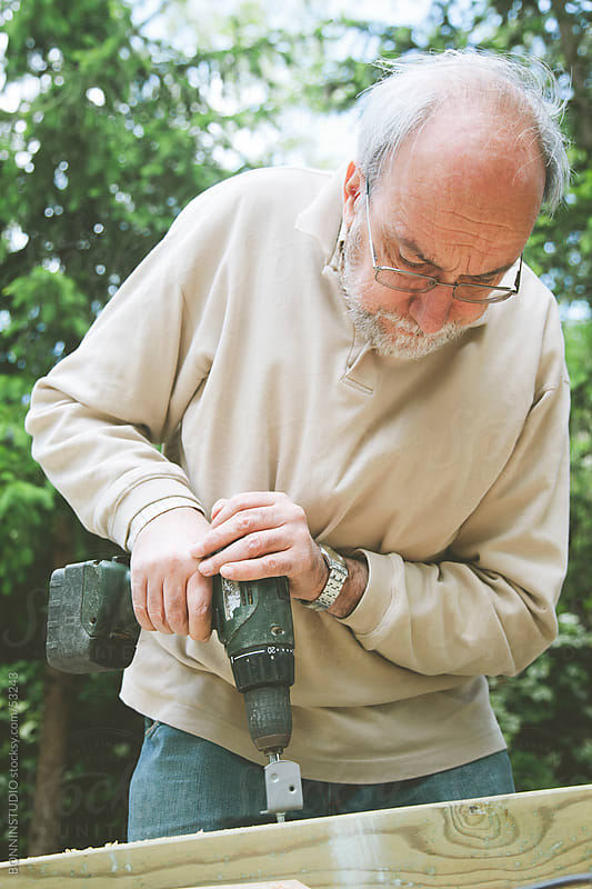 Old man with drill in outdoors making carpenter work at his garden.  by BONNINSTUDIO for Stocksy United