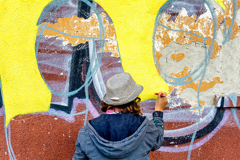 Female graffiti artist painting on wall by Pixel Stories for Stocksy United