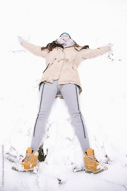 Young woman making snow angel in park by T-REX & Flower for Stocksy United