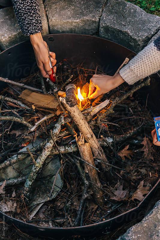 Friends lighting a fire by Jen Grantham for Stocksy United