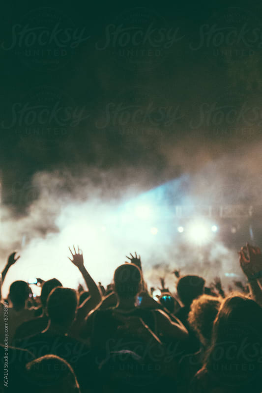 Blurred spectators at a concert in the evening by ACALU Studio for Stocksy United