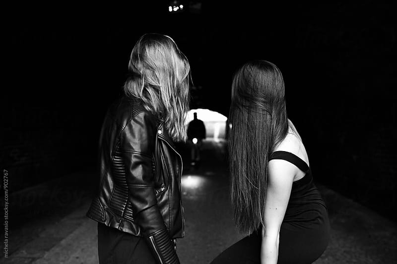 Two women looking at bike in the tunnel by michela ravasio for Stocksy United