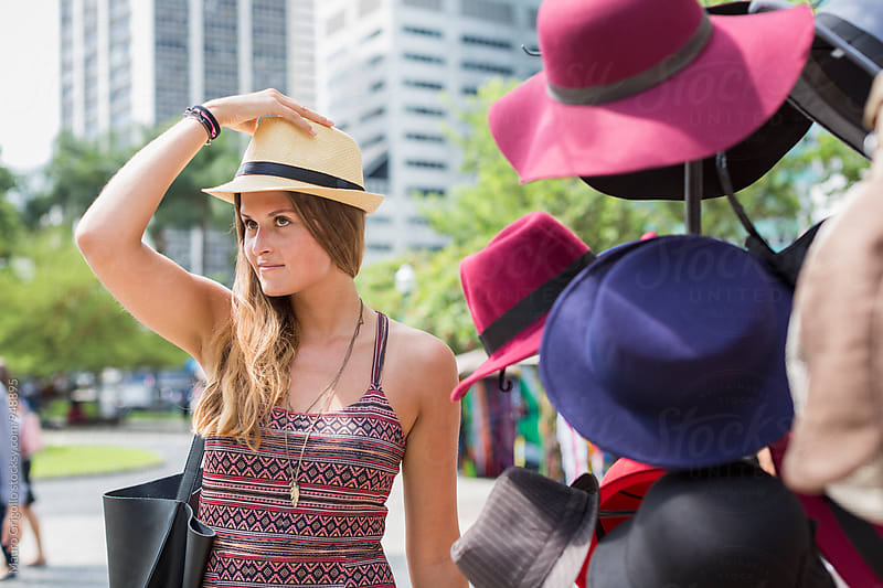 Woman searching for a hat in a market. Rio de Janeiro. Brazil. by Mauro Grigollo for Stocksy United
