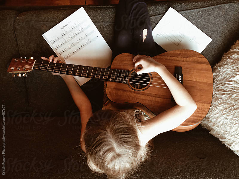Young girl practicing the guitar by Kristin Rogers Photography for Stocksy United