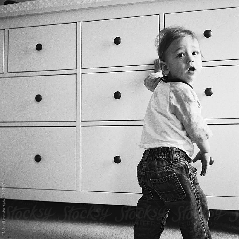 Toddler practicing standing up in black and white square by Meghan Boyer for Stocksy United
