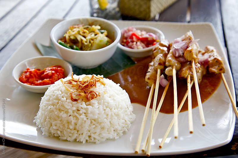 An appetising plate of asian side dishes with rice, chicken sticks and satay sauce, Bali, Indonesia by Jaydene Chapman for Stocksy United