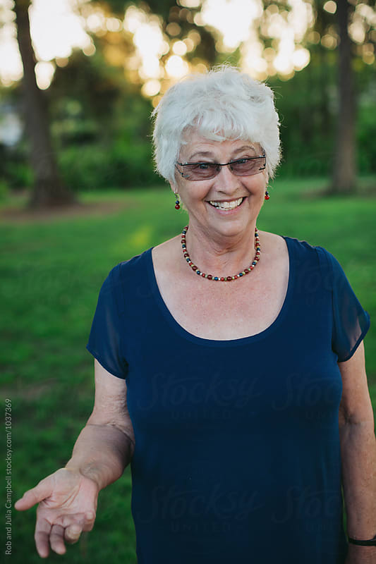 Happy caucasian senior woman smiling at camera outside by Rob and Julia Campbell for Stocksy United