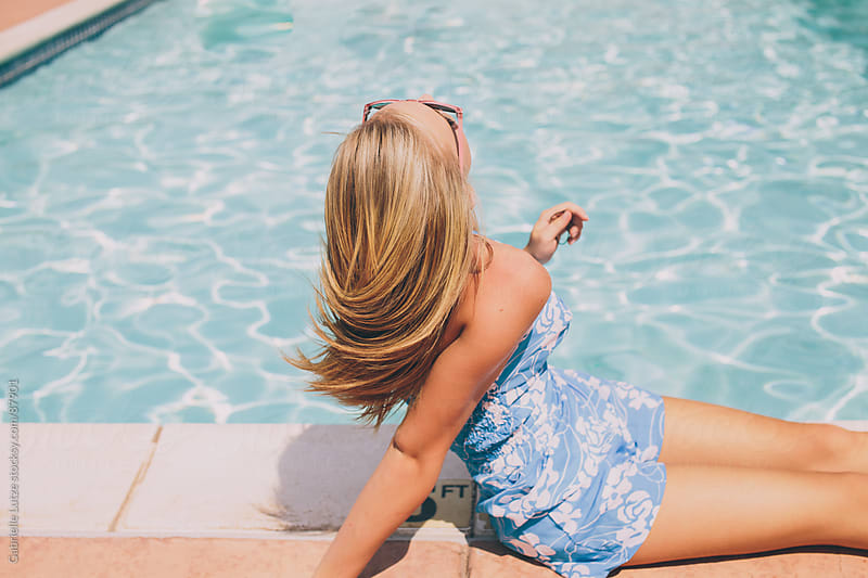 Pretty Girl Lying Down by Pool by Gabrielle Lutze for Stocksy United