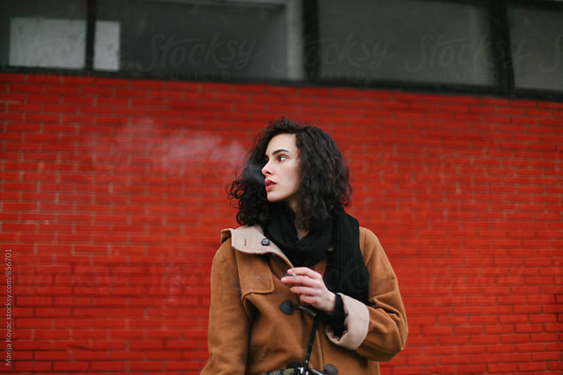 Brunette woman smoking, red background  by Marija Kovac for Stocksy United