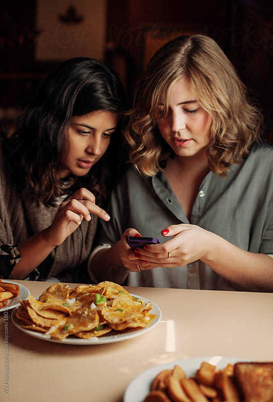 Friends using smart phone at a restaurant  by W2 Photography for Stocksy United
