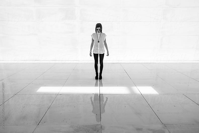 Young stylish woman standing on a big white water space wearing rounded sunglasses. by BONNINSTUDIO for Stocksy United