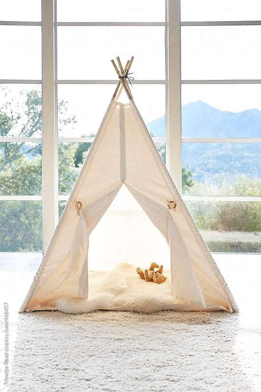 Kid's teepee tent in living room with stuffed animals inside by Trinette Reed for Stocksy United