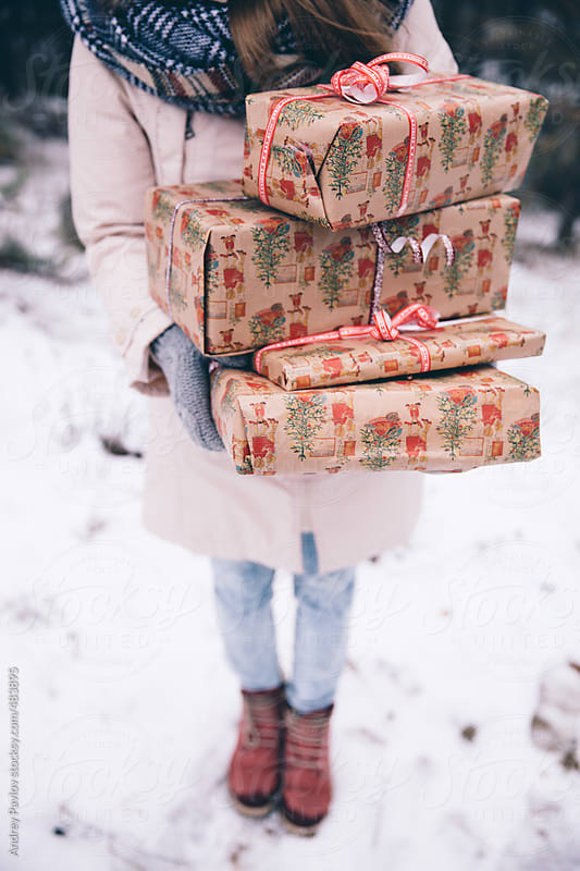 Girl carries an armload of gifts by Andrey Pavlov for Stocksy United