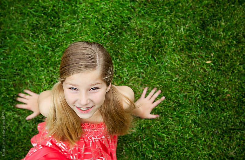 Grass: Cute Girl Sitting in Grass by Sean Locke for Stocksy United