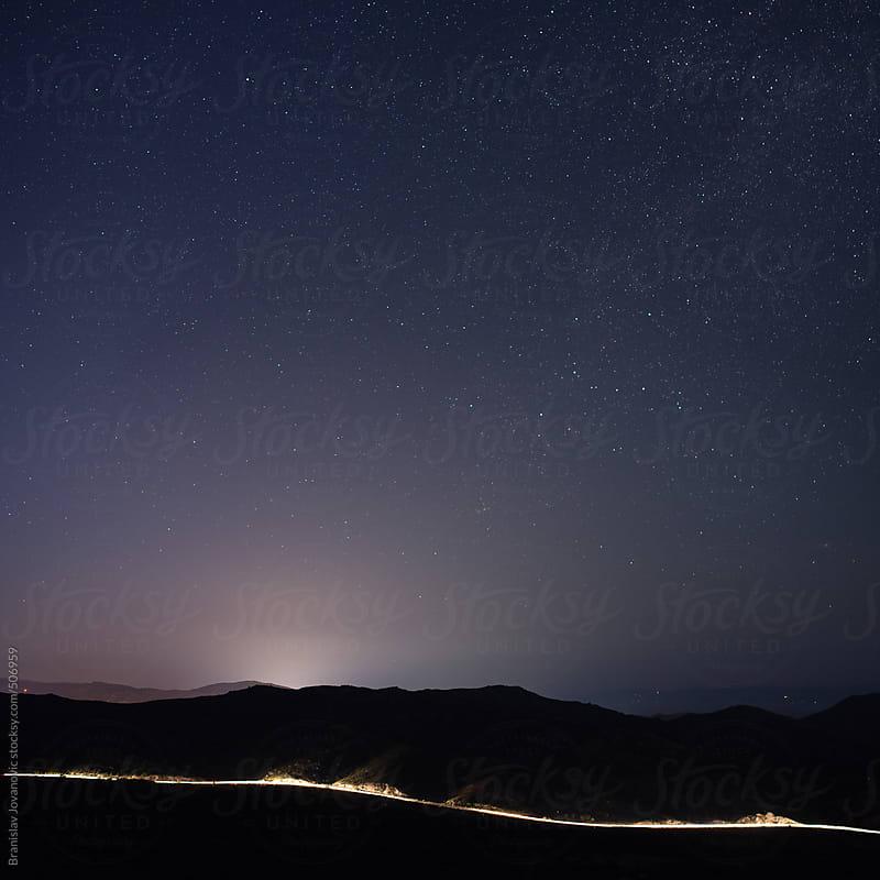 Night sky and illuminated mountain road by Brkati Krokodil for Stocksy United