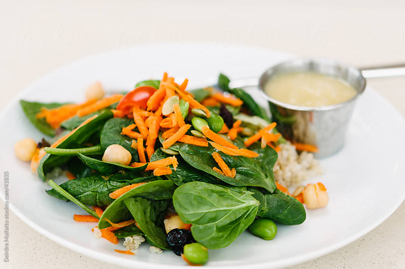 Spinach salad with carrots and chickpeas and dressing by Deirdre Malfatto for Stocksy United