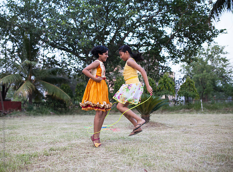 Two girls playing with jumping rope and making fun in outdoor by PARTHA PAL for Stocksy United