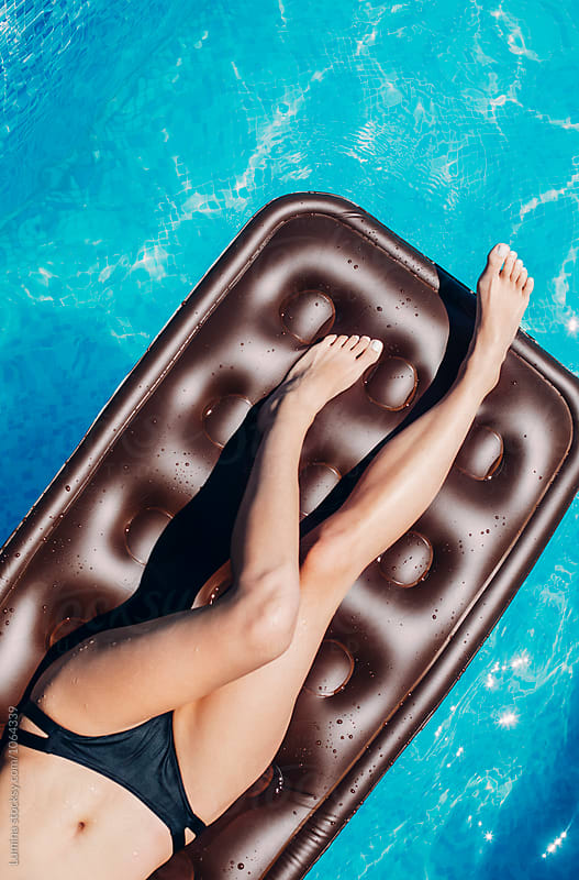 Woman on a Water Mattress at the Swimming Pool by Lumina for Stocksy United