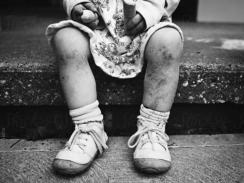 Little girl sits on step in a dress with dirt on her legs by Maria Manco for Stocksy United