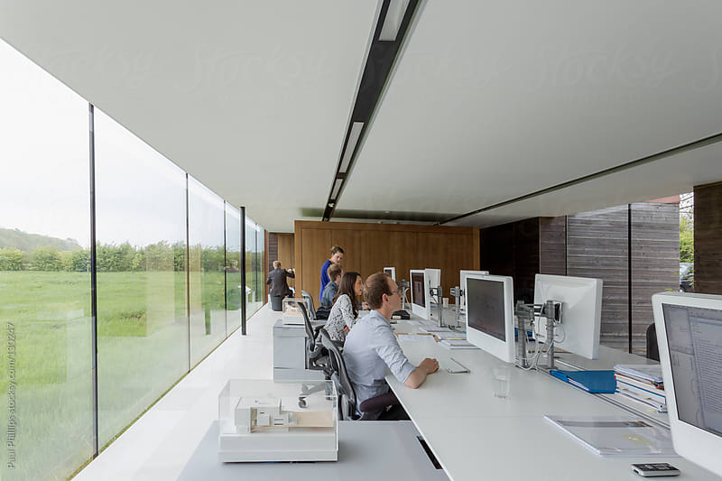 Modern office with computer monitors and four staff behind desks by Paul Phillips for Stocksy United