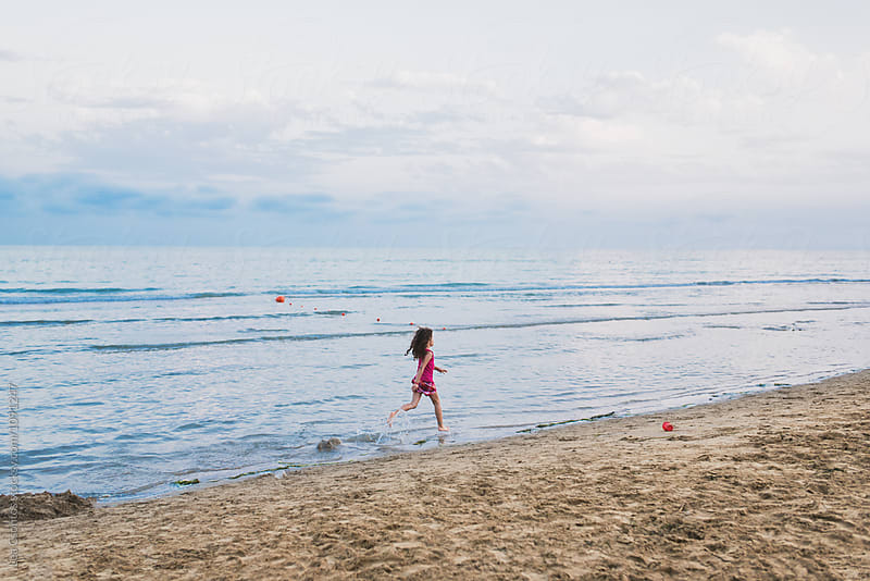 Little girl running along the seashore in the evening by Lea Csontos for Stocksy United