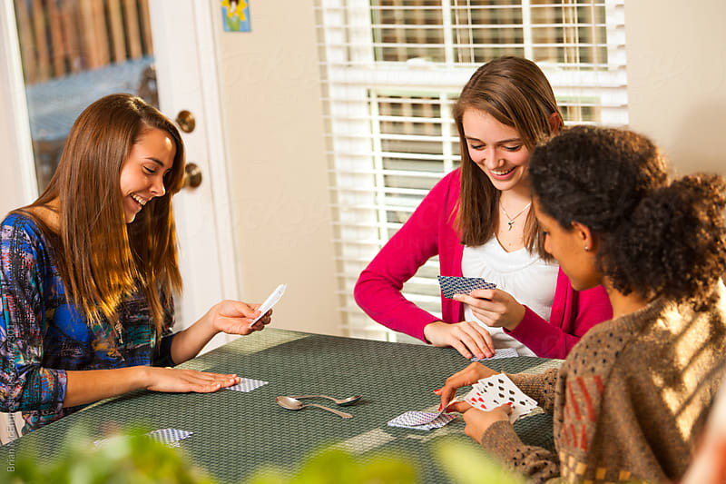Multi-ethnic Group of Young Women Playing Cards by Brian McEntire for Stocksy United