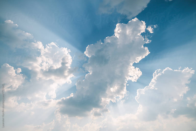 sun beams striking through beautiful blue cloudy sky by Leander Nardin for Stocksy United