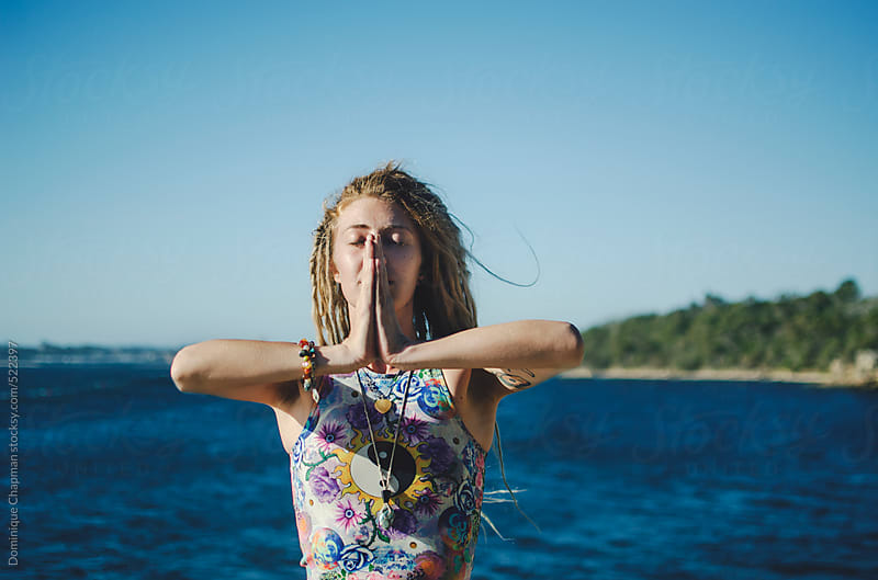 Young woman doing yoga by ocean by Dominique Chapman for Stocksy United