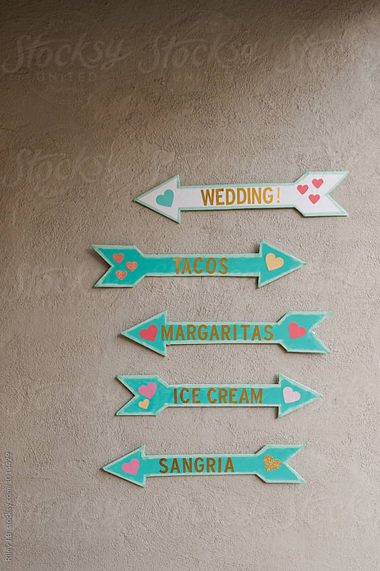 Direction arrows on a wall at a wedding by Riley J.B. for Stocksy United