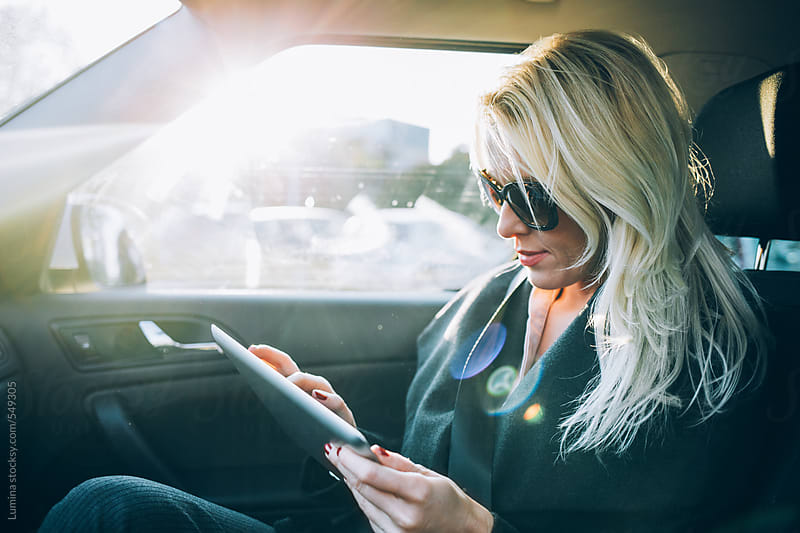 Woman Using a Tablet in a Car by Lumina for Stocksy United