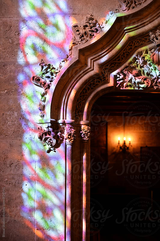 Colors of a stained glass window reflected in a stone wall by Bisual Studio for Stocksy United