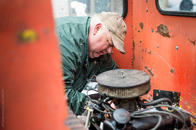 Overweight Man Auto Mechanic Repairing Old Engine on Rusty Farm Machenery by JP Danko for Stocksy United