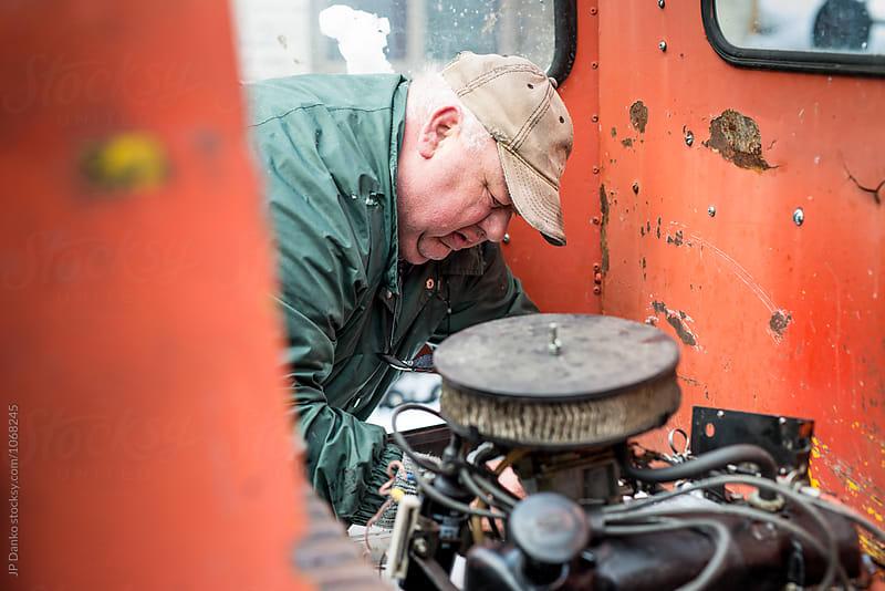 Overweight Man Auto Mechanic Repairing Old Engine on Rusty Farm Machenery by JP Danko for Stocksy United