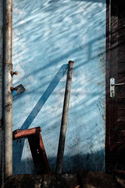 Objects Leaning on a Blue Wall by Gary Radler Photography for Stocksy United