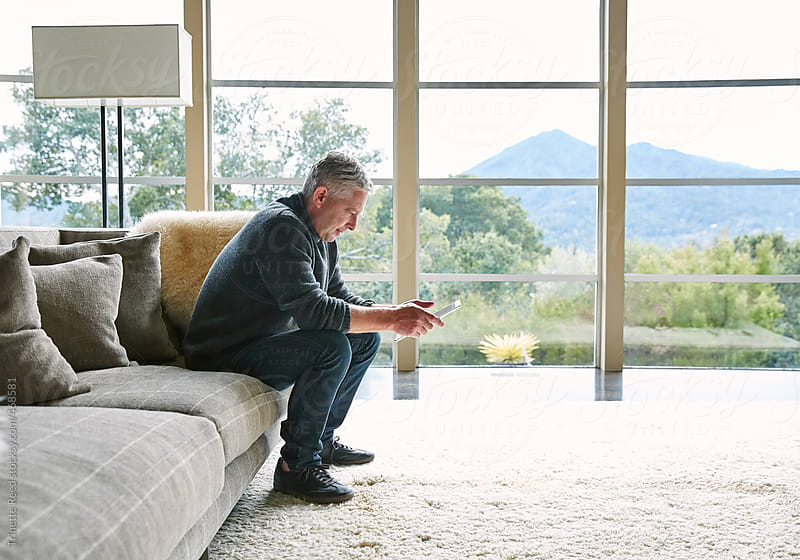 Mature man with grey hair looking at digital tablet on living room sofa by Trinette Reed for Stocksy United