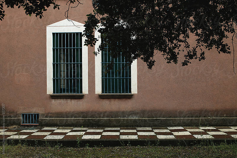 Old house with two windows and red wall by Miquel Llonch for Stocksy United