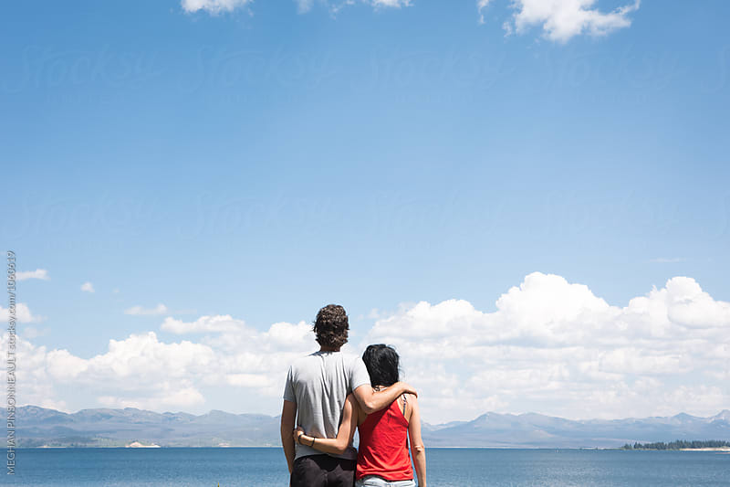 Couple Standing by Lake with Blue Sky by MEGHAN PINSONNEAULT for Stocksy United