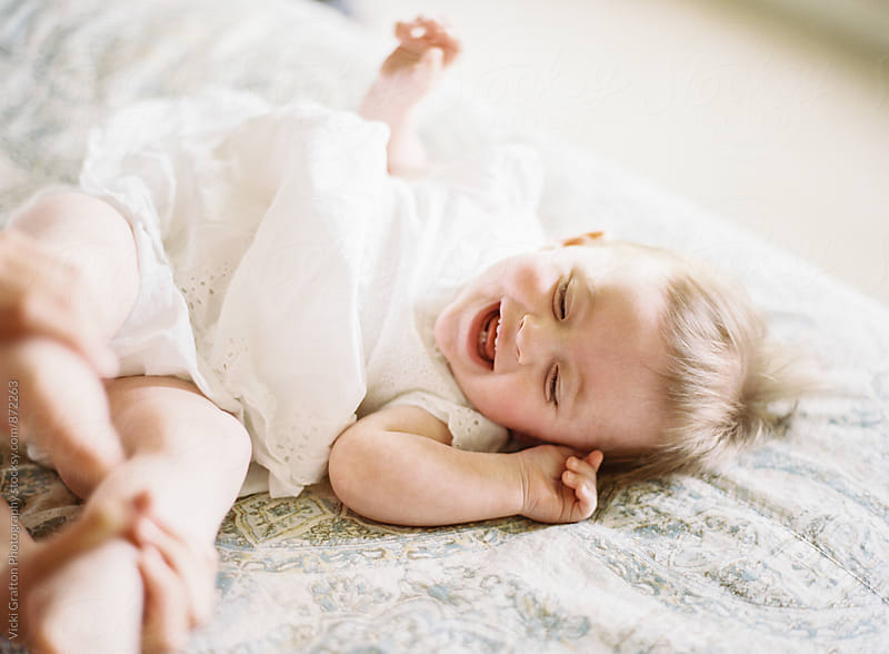 1 year old playing on bed  by Vicki Grafton Photography for Stocksy United