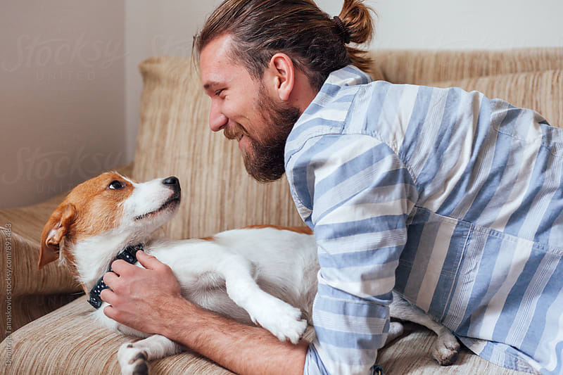 Man having fun with his jack russell dog by Dimitrije Tanaskovic for Stocksy United