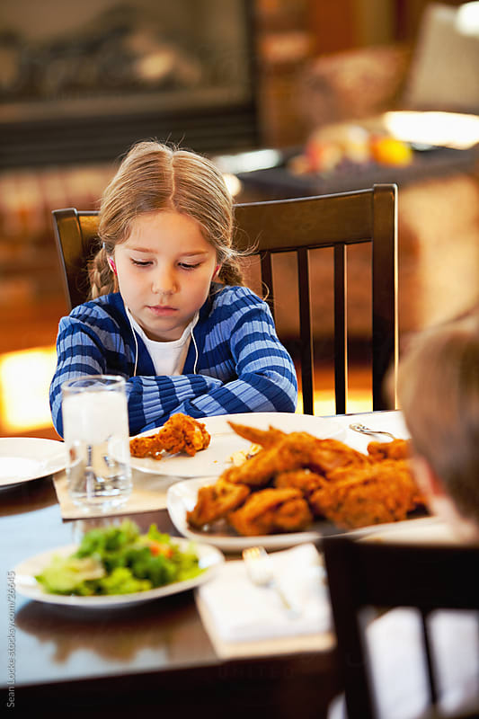 Family: Girl with Headphones Not Happy at Dinner by Sean Locke for Stocksy United